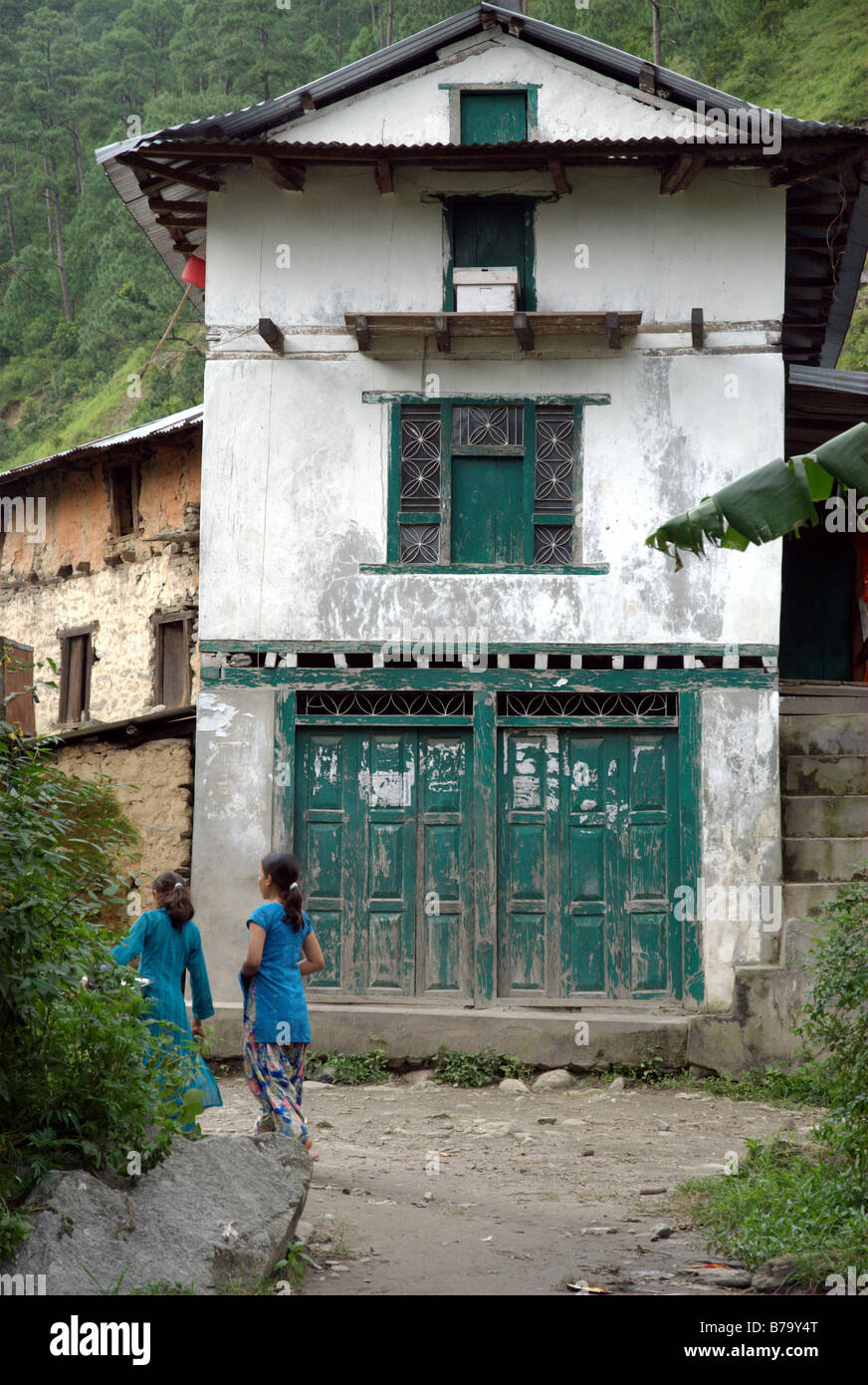 Two girls walk by a house in the village of Singati Bazar, Tamakoshi Valley, Dolakha district, Nepal - Stock Image