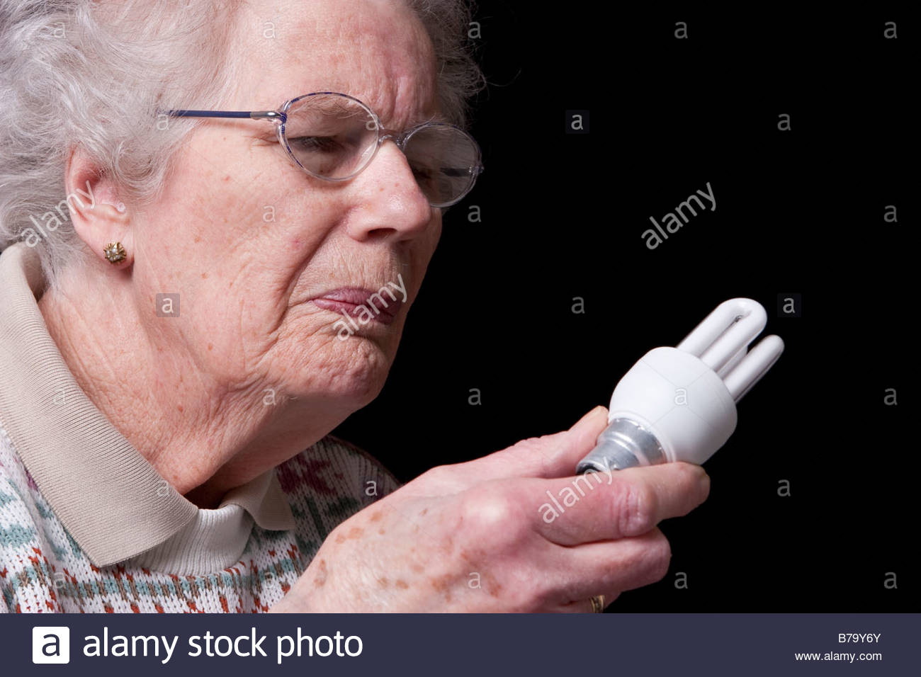 An old woman holding a low energy lightbulb. - Stock Image