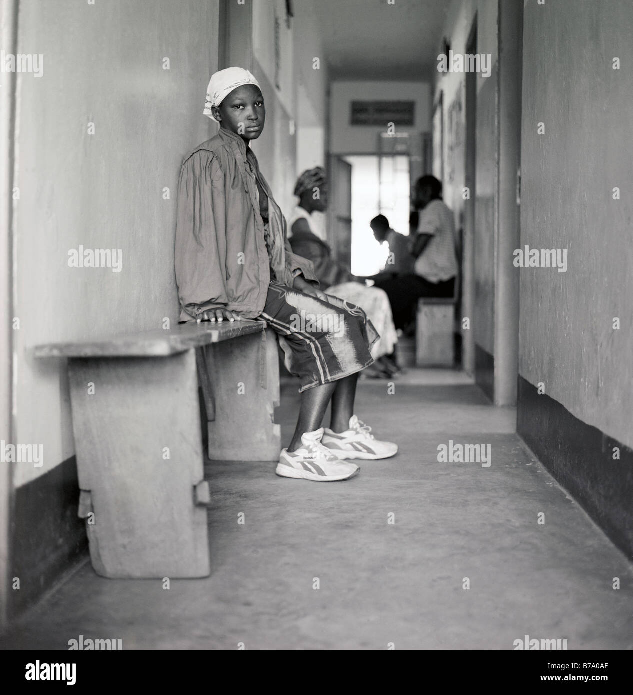 Lady sitting in a corridor in a health clinic treatment centre in Ndejje Uganda - Stock Image