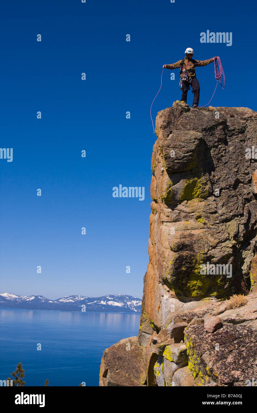 A mountaineer standing on top of a cliff above lake tahoe in Nevada coiling his climbing rope - Stock Image