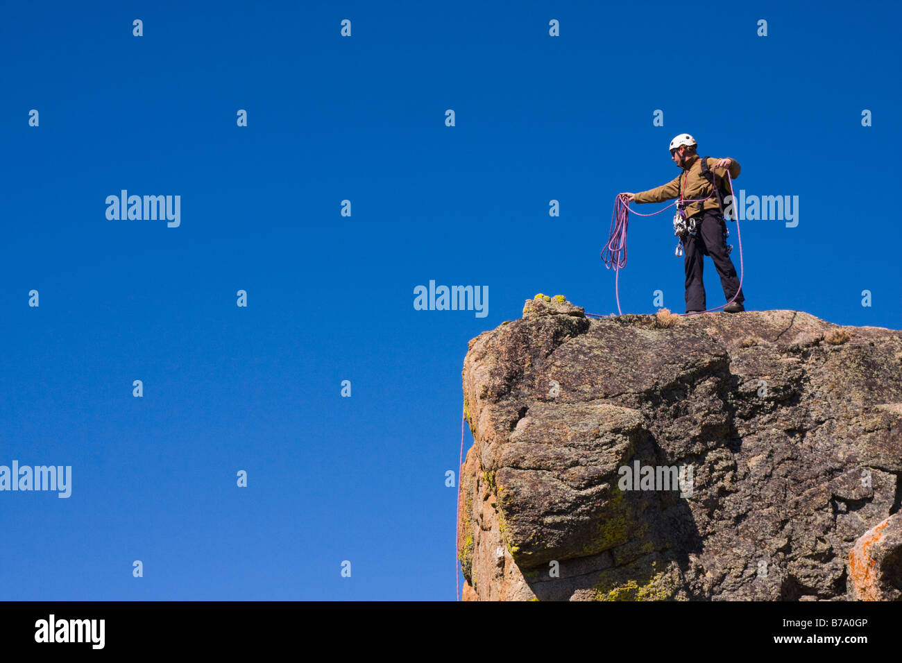 A mountaineer standing on top of a cliff coiling his climbing rope - Stock Image