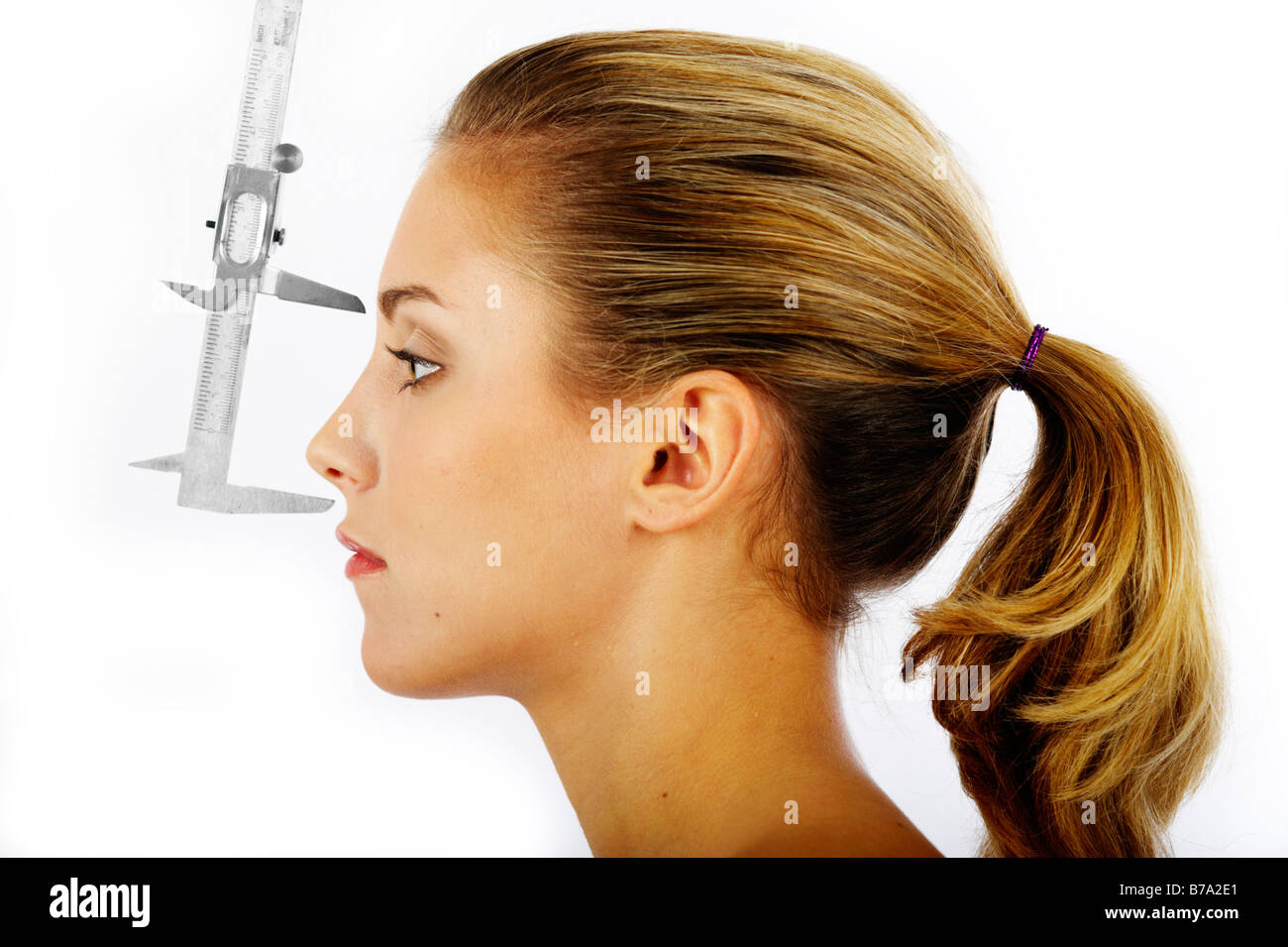 Young woman, distance between the forehead and the nose being measured with a caliper rule - Stock Image
