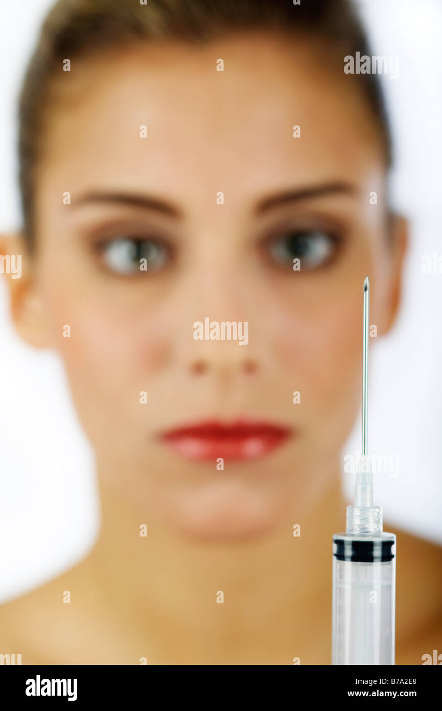 Young woman and an injection needle - Stock Image
