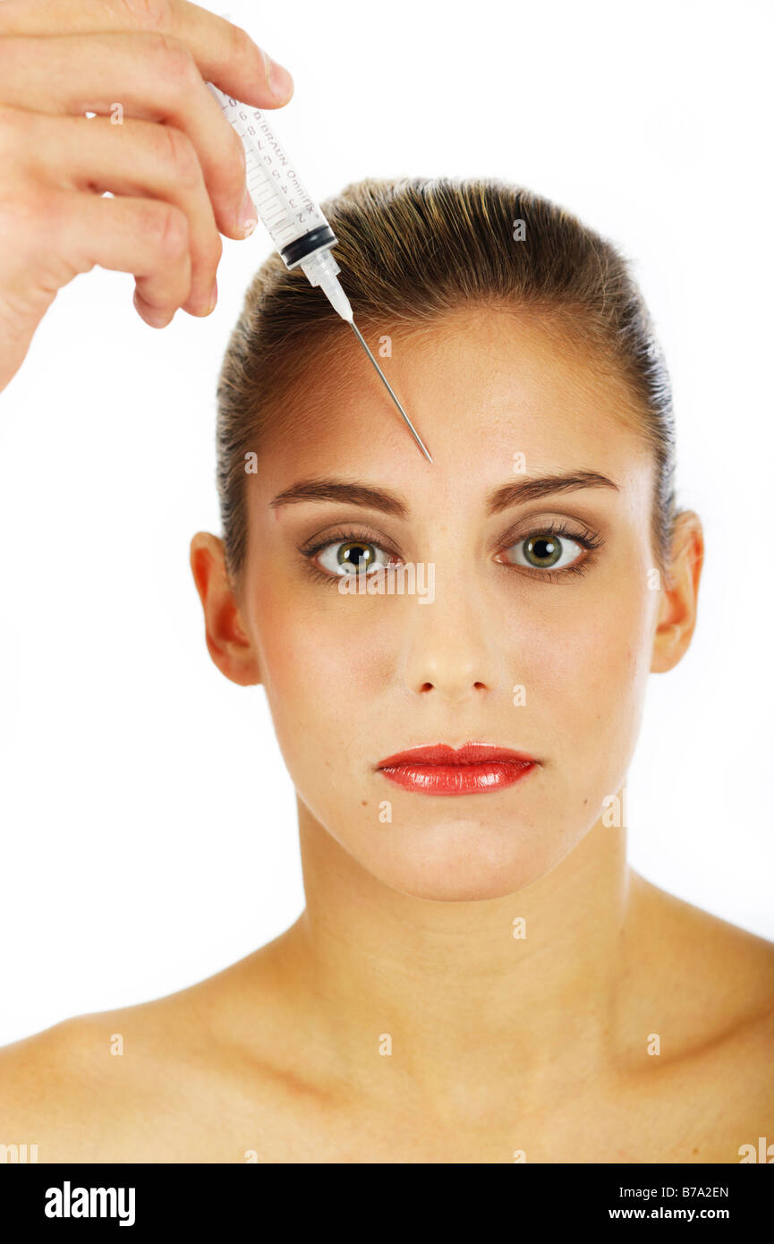 Young woman getting an injection against forehead wrinkles - Stock Image
