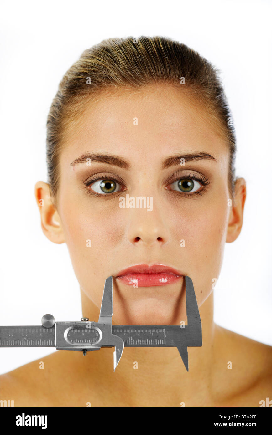 Woman's mouth being measured with a caliper rule - Stock Image
