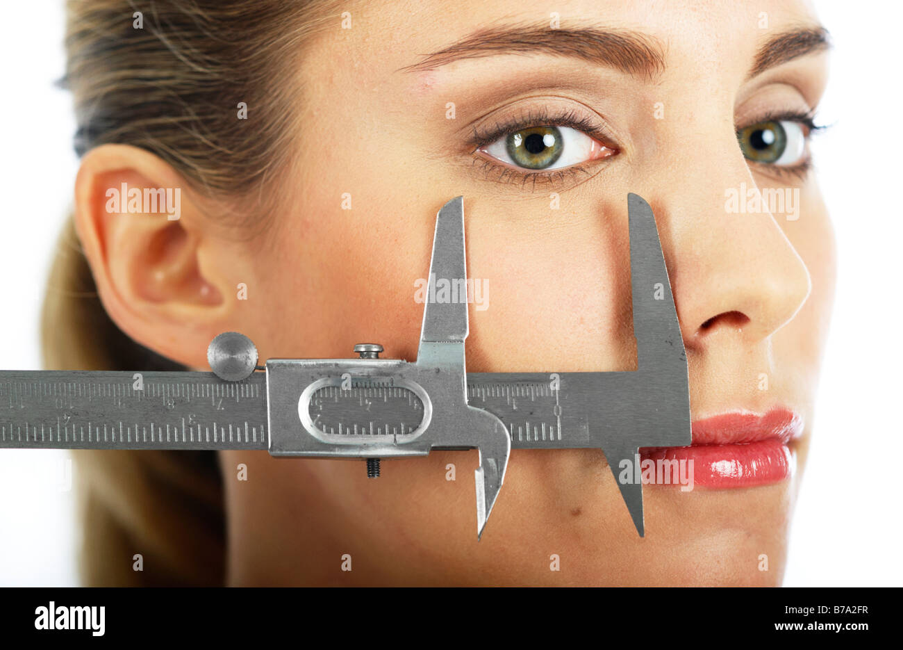 Width of a young woman's eye being measured with a caliper rule - Stock Image