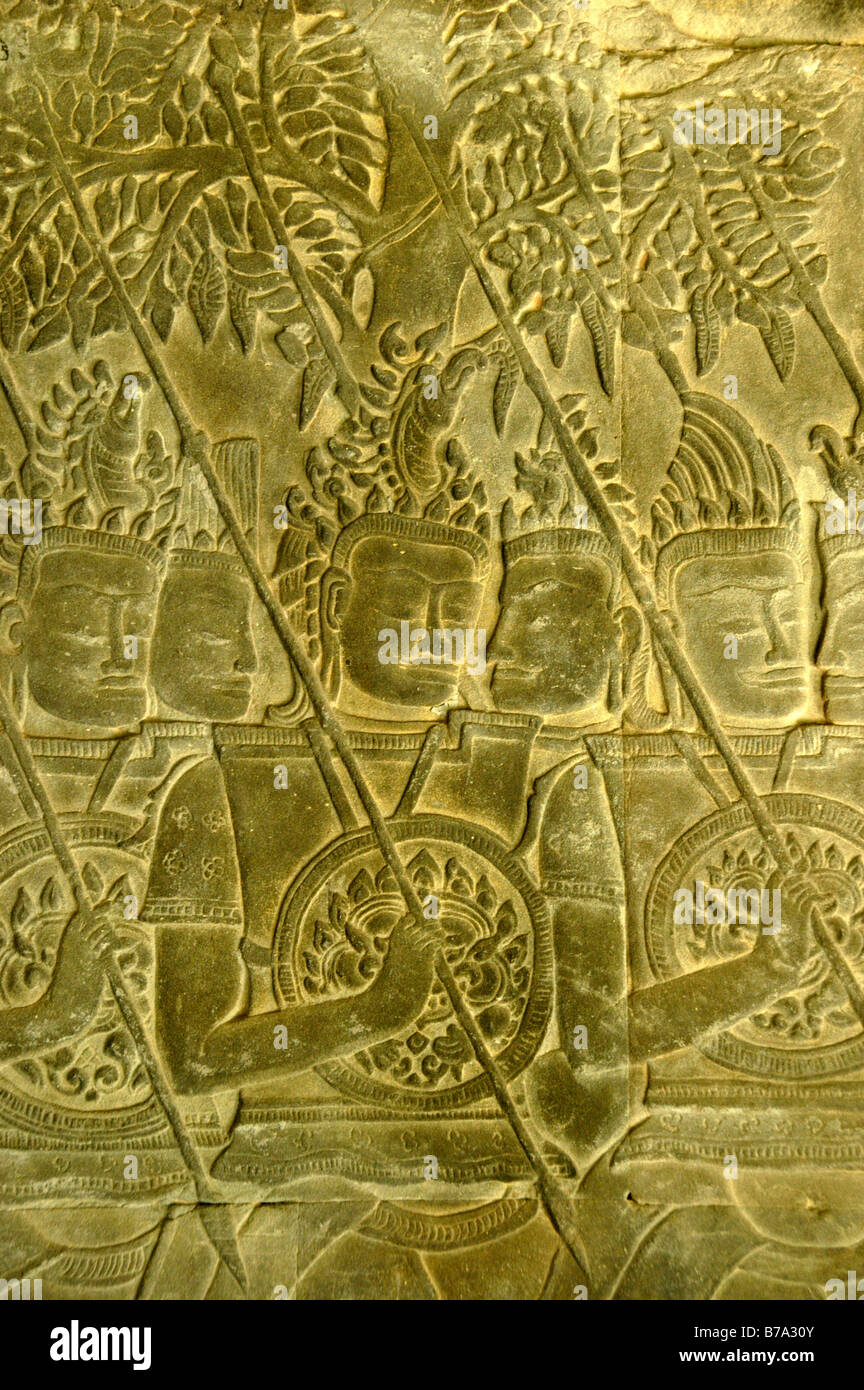 Intricate stone relief, warriors with spears and shields in front of trees, Angkor Wat Temple, Siem Reap, Cambodia, - Stock Image