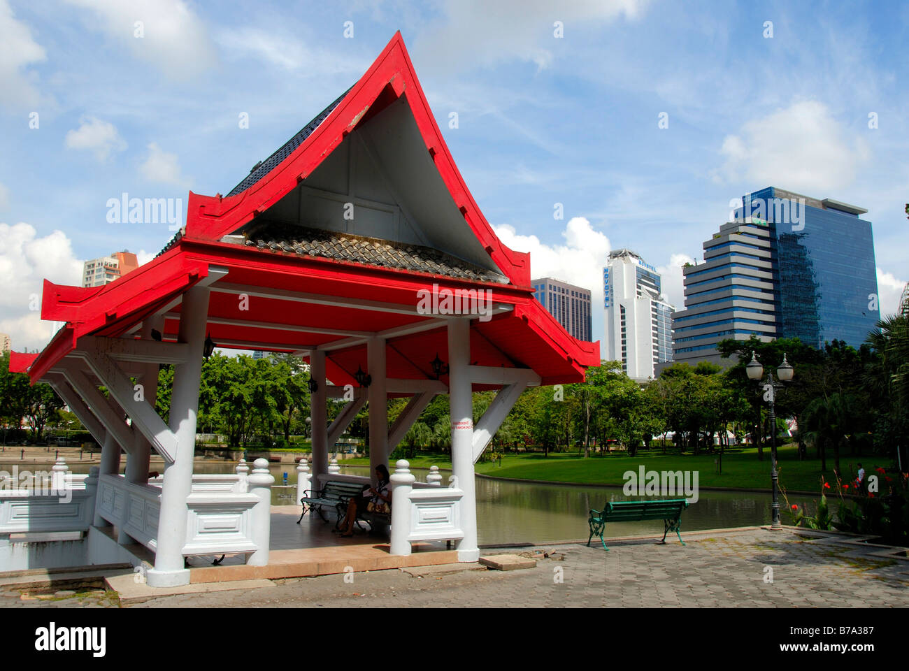 Small temple with a red roof in front of modern multistory buildings, Queens Park, Bangkok, Thailand, Southeast - Stock Image