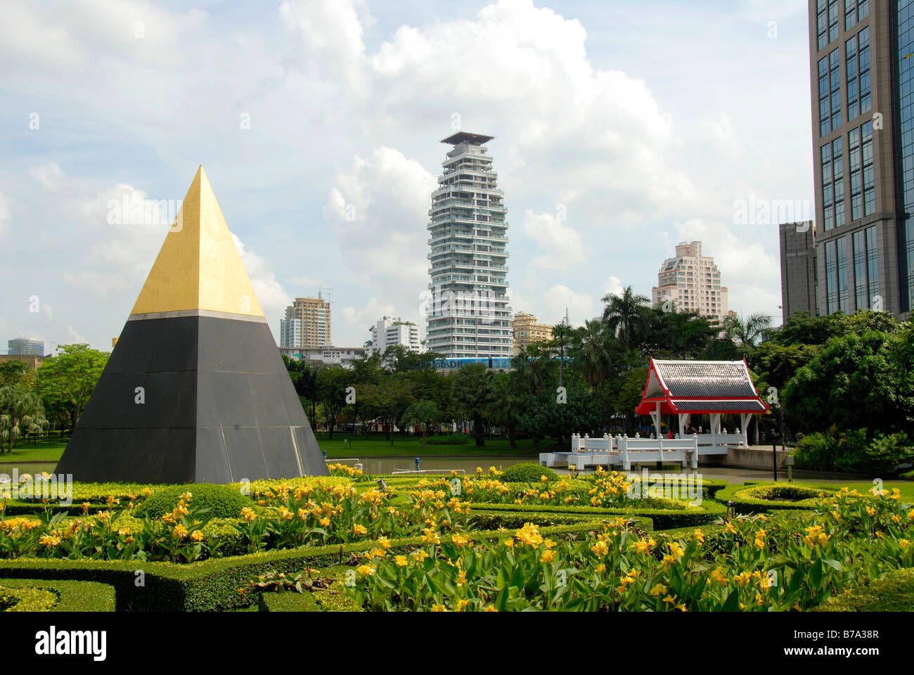 Pyramid with a golden peak in front of a temple and modern multistory buildings, Queens Park, Bangkok, Thailand, - Stock Image