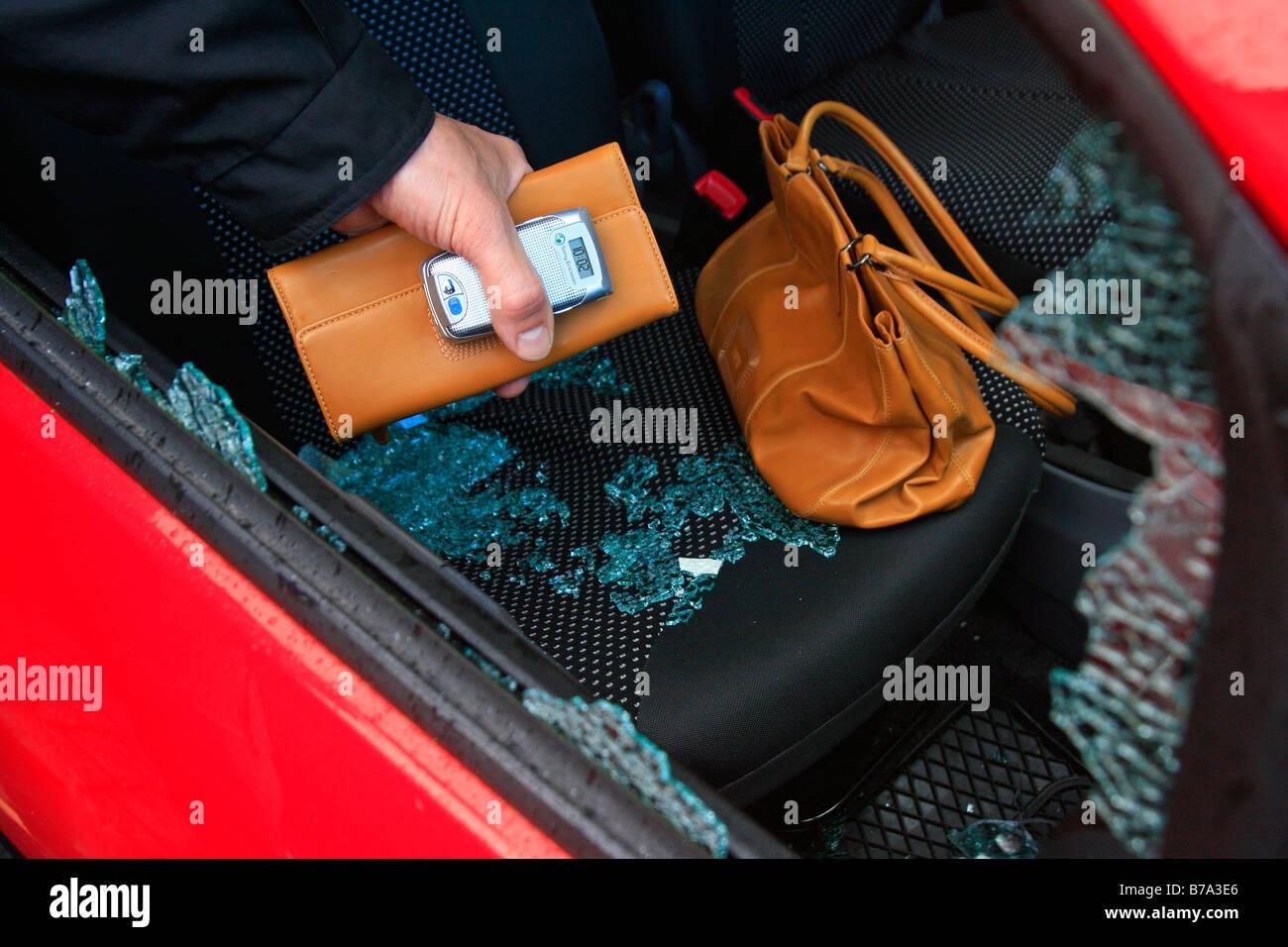 Car burglary, hand grasps through the side window at valuables, i.e. handbag, purse and mobile phone - Stock Image