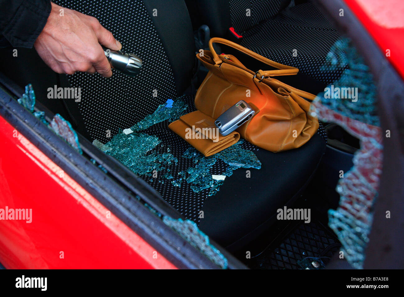 Car burglary, hand holds a torch through the broken side window on the look out for valuables, i.e. handbag, purse - Stock Image