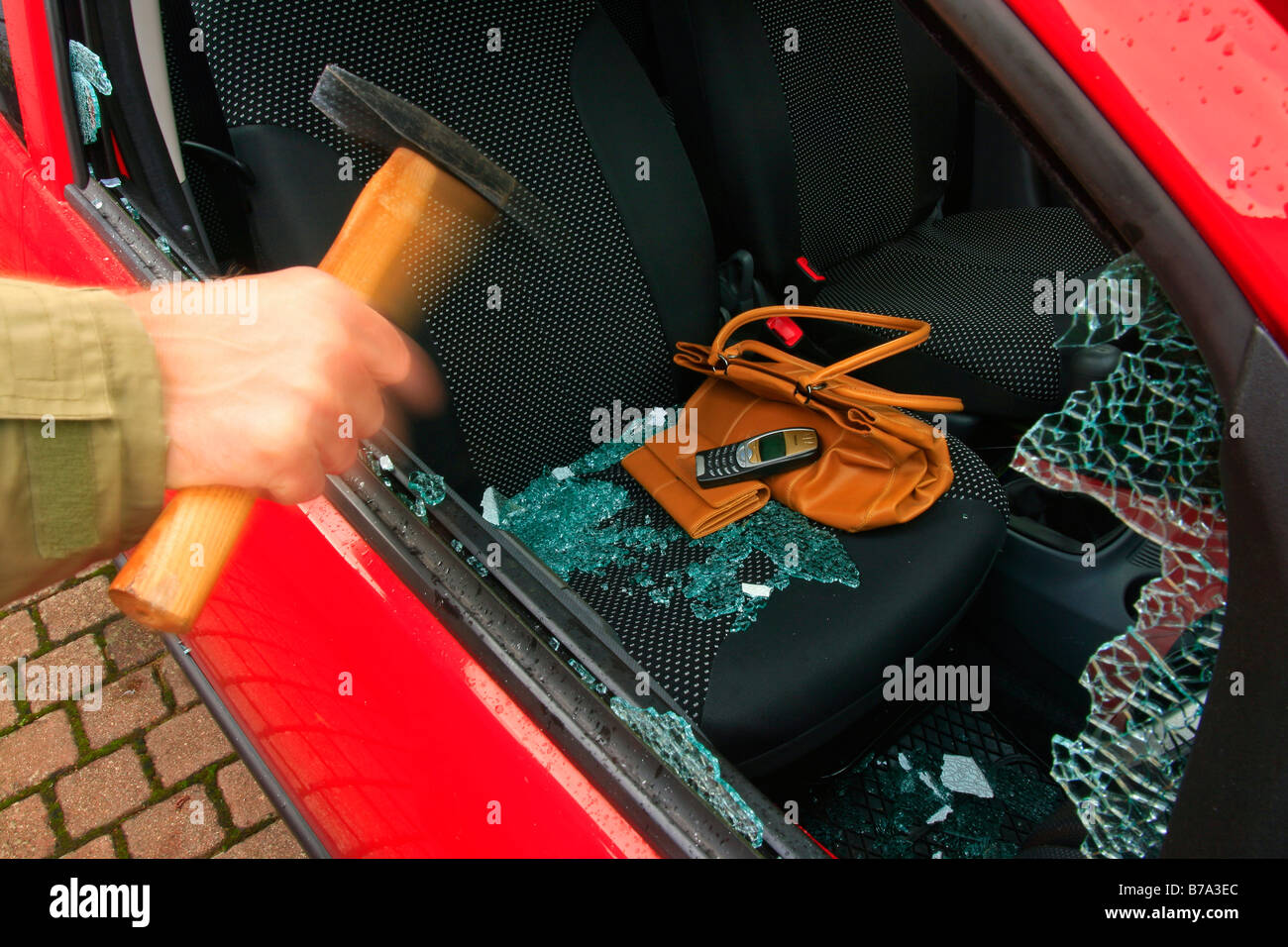 Car burglary, hand with hammer batters the side window, valuables left on the passenger seat, i.e. handbag, purse - Stock Image