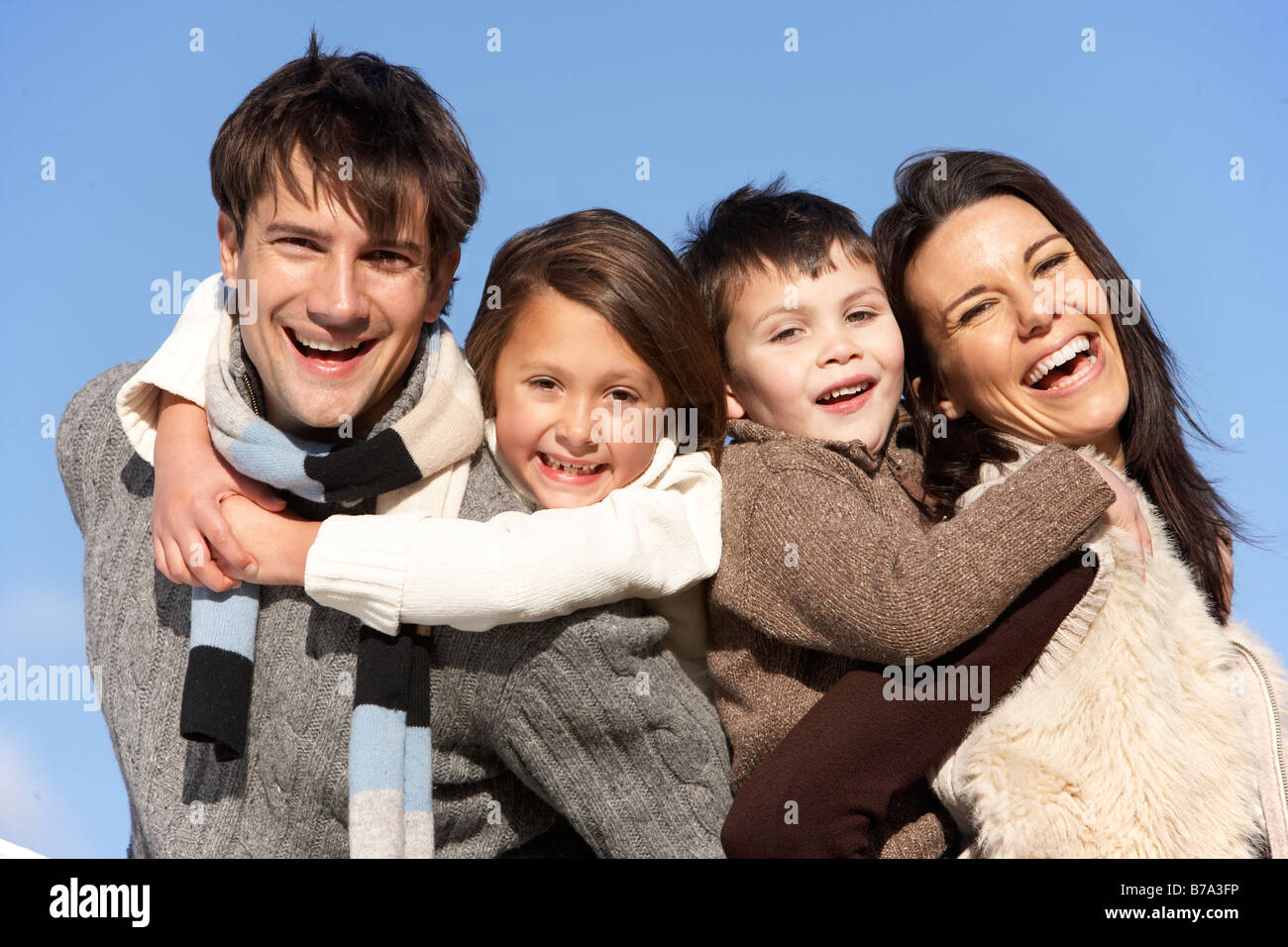 Parents Piggy Backing Their Children - Stock Image
