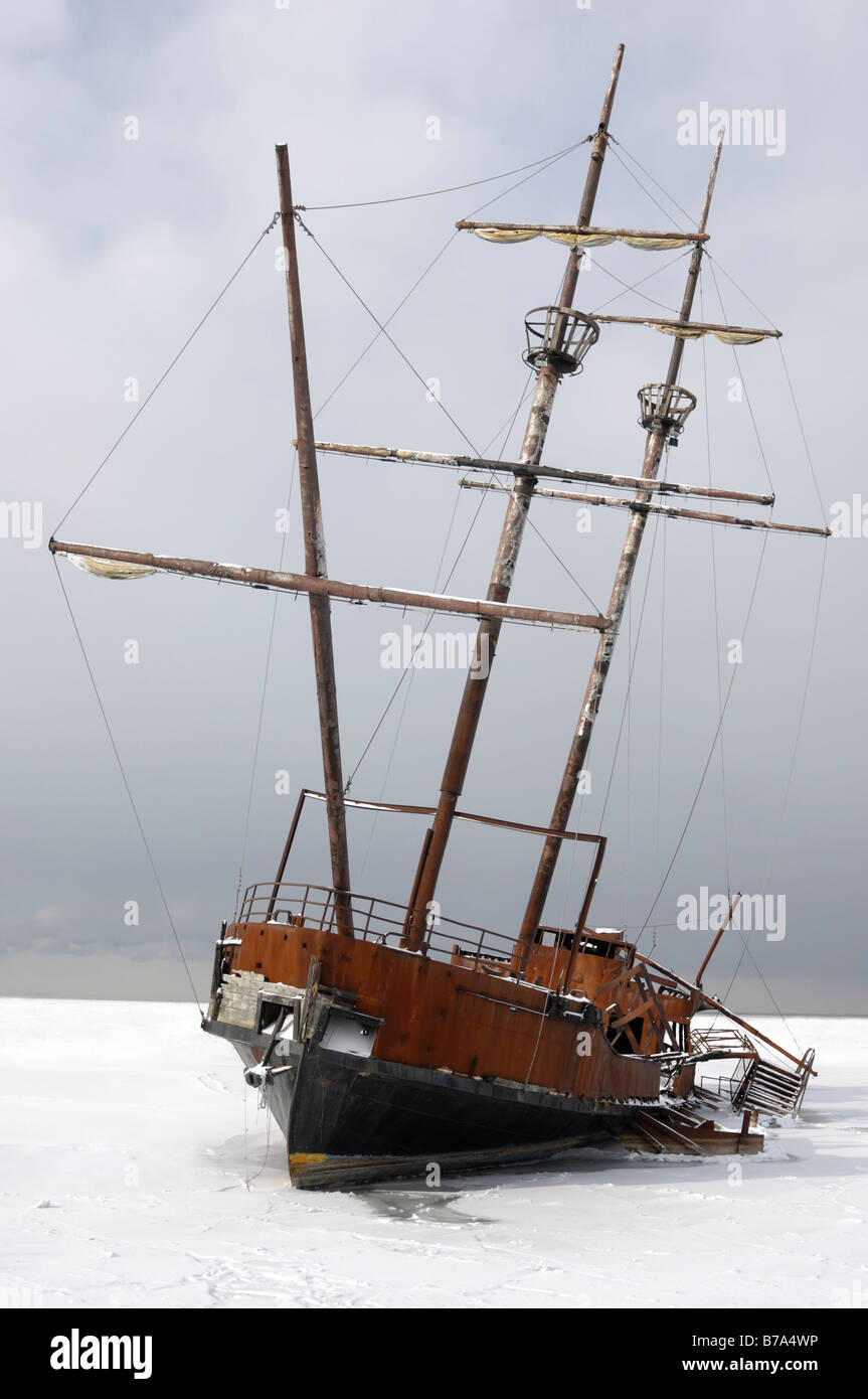Rusting grounded ship in frozen water - Stock Image