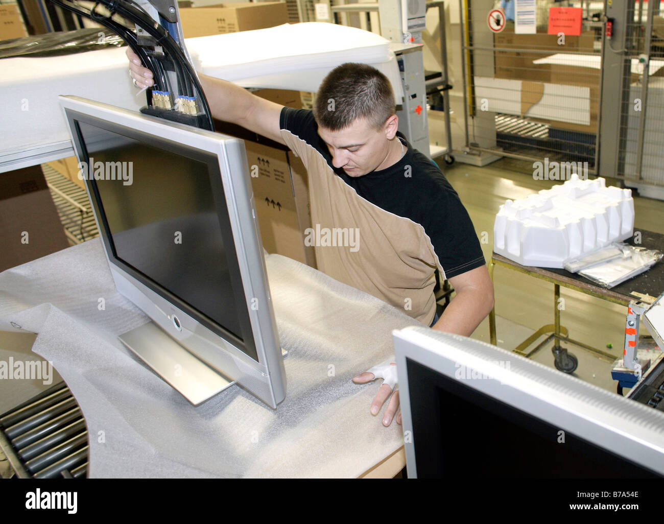 Employee packing a Loewe LCD television with flat panel display at Loewe AG factory in Kronbach, Bavaria, Germany - Stock Image