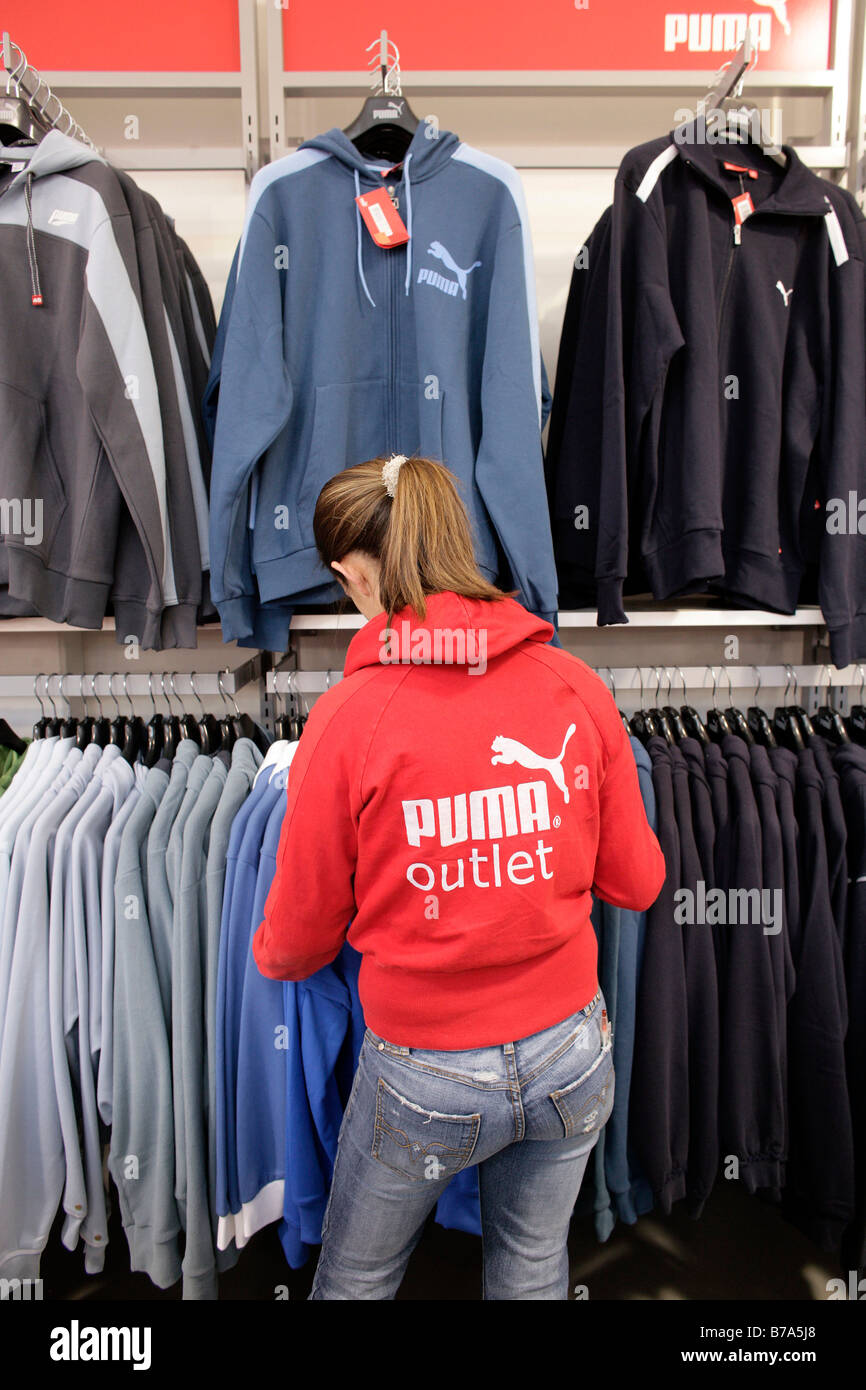 Sales assistant sorting sports jackets in the Puma outlet ...