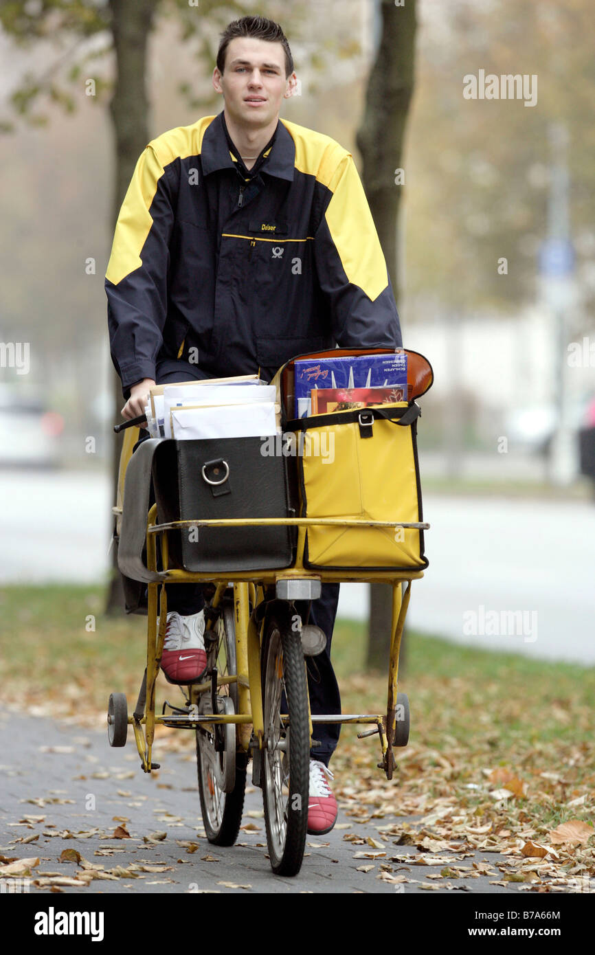 Mailman of the Deutsche Post AG, German post, on a bike in Regensburg, Bavaria, Germany, Europe - Stock Image
