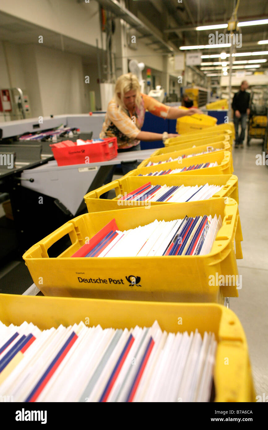 Employee of the Deutsche Post AG, German post, working on a machine that sorts the letters into the right order - Stock Image