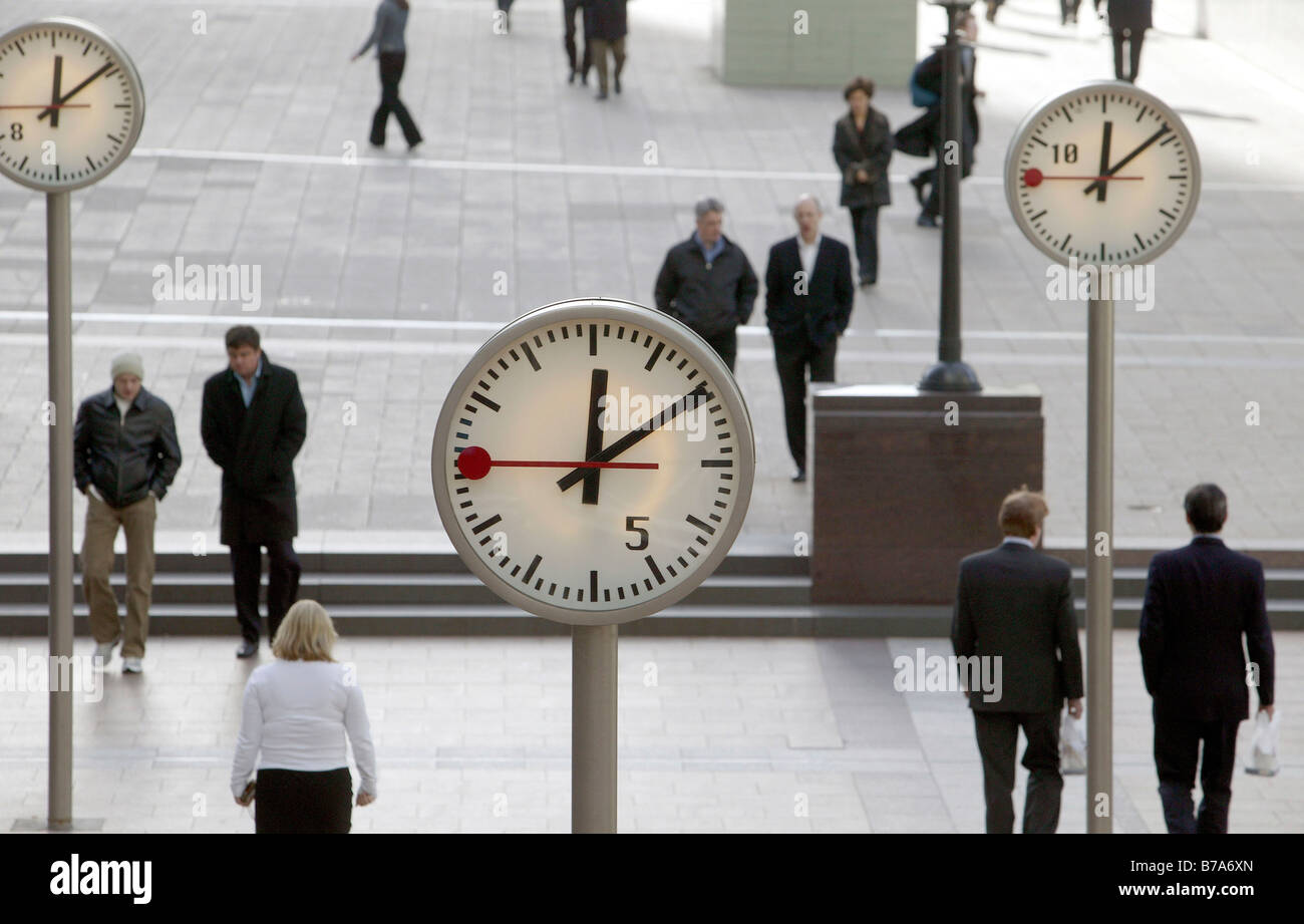 Public place with clocks in Canary Wharf in London, England, Great Britain, Europe - Stock Image