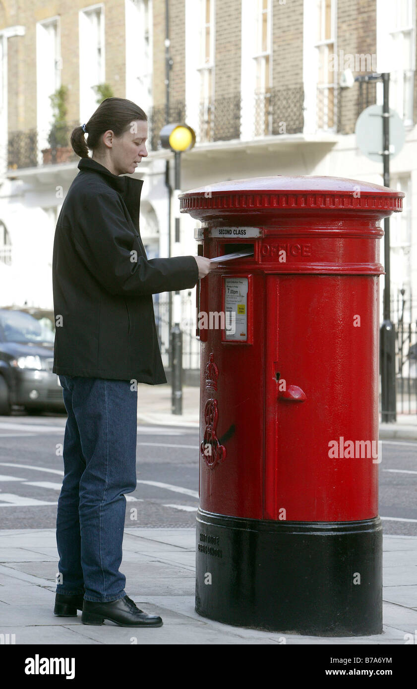 Woman throwing letter into a postbox of the Royal Mail in London, England, Great Britain, Europe Stock Photo