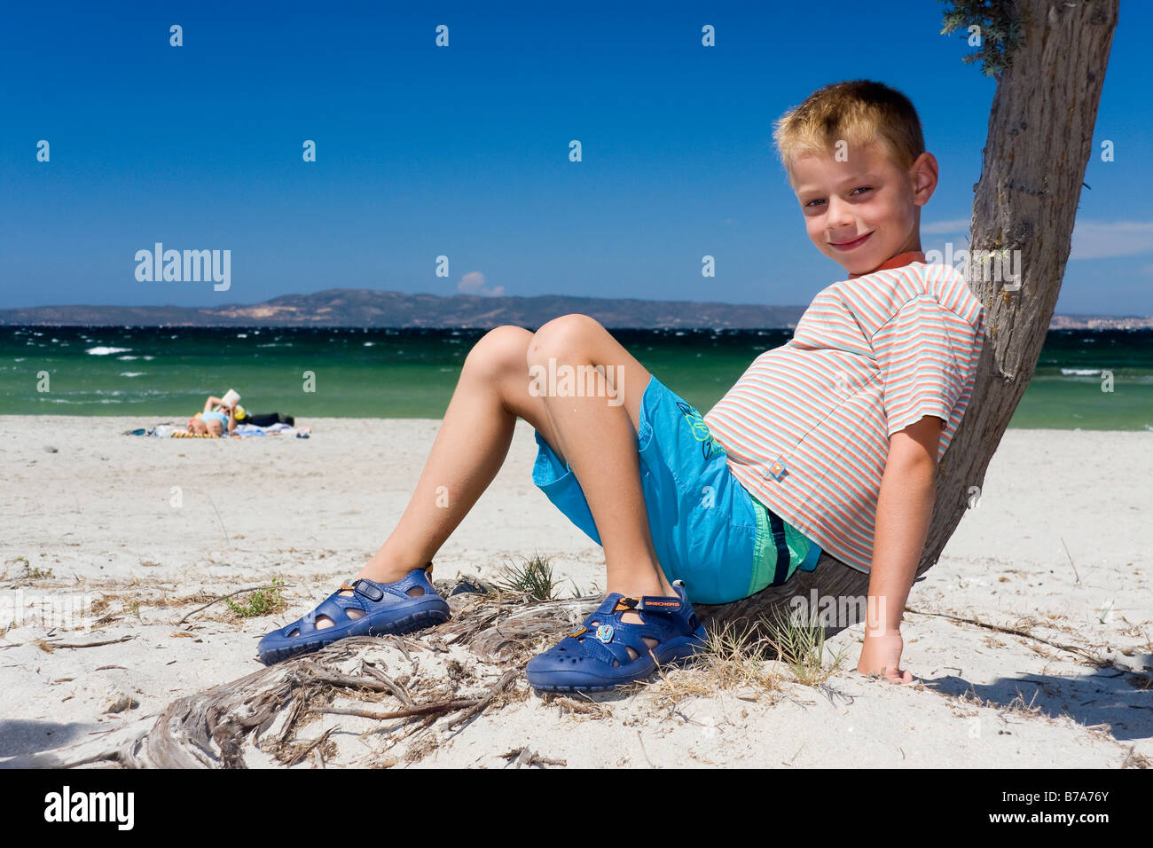 6-year-old boy leaning against a tree at the beach - Stock Image