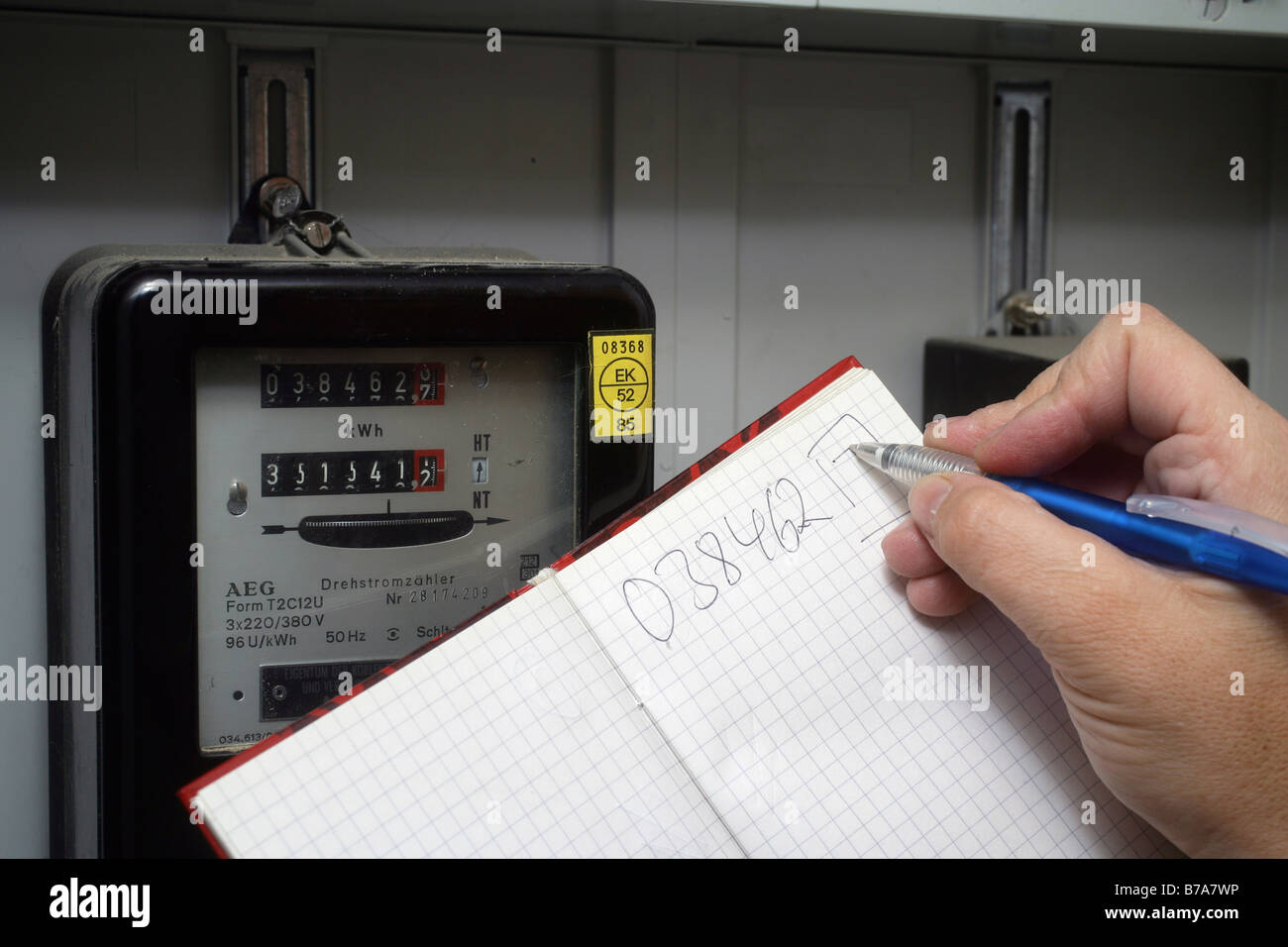 Hand taking note of electricity consumption, electricity meter in detached house, Koblenz, Rhineland-Palatinate, Stock Photo