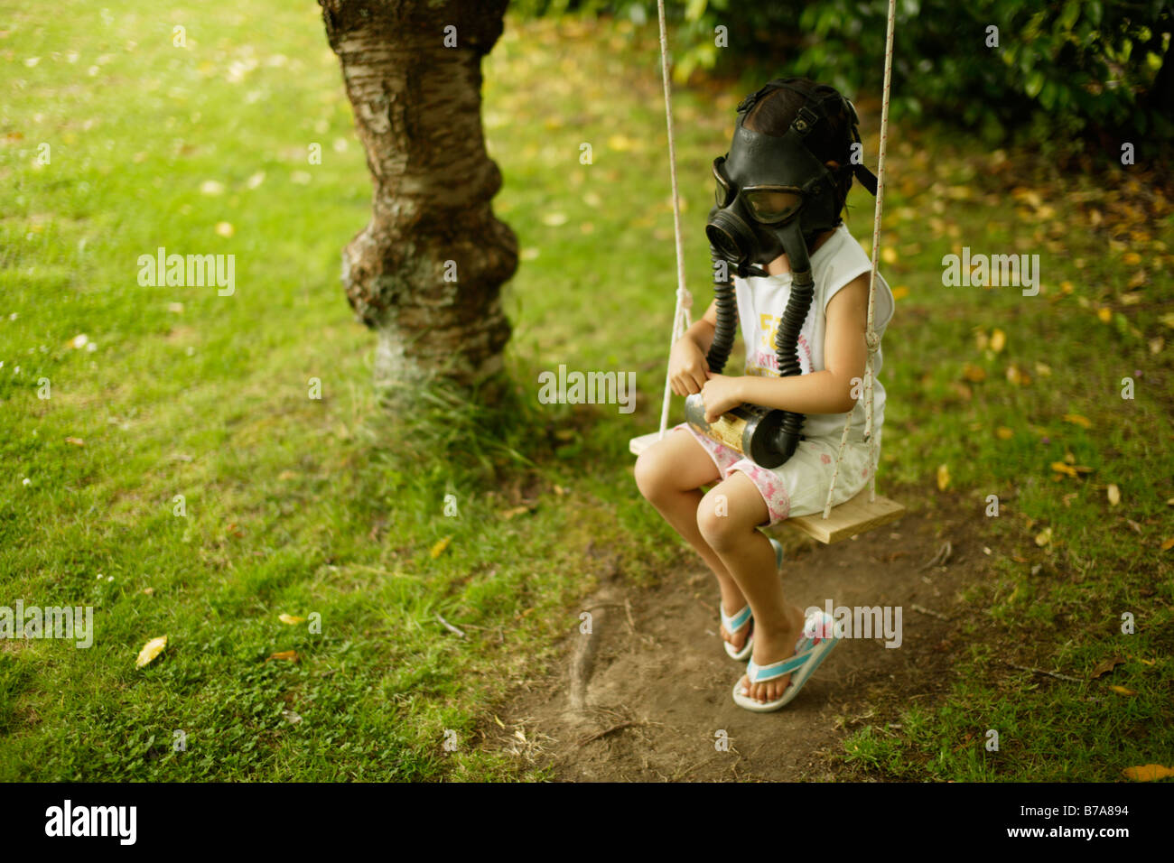 Five year old girl sits on swing wearing a gas mask - Stock Image