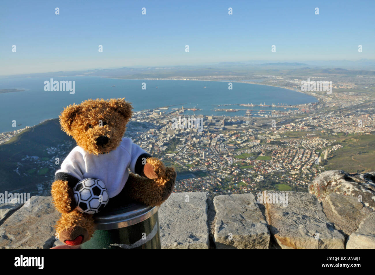 Soccer teddy bear in front of a view over Cape Town from Table Mountain, South Africa - Stock Image