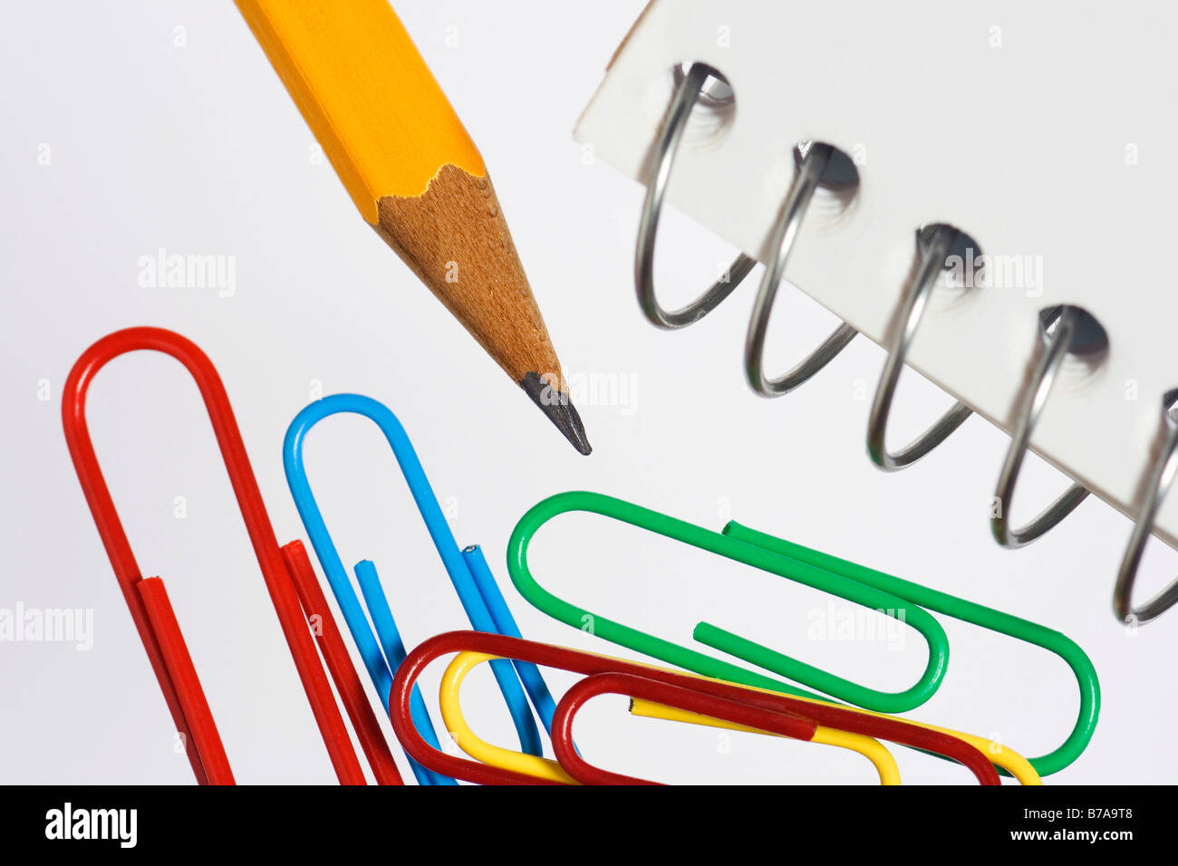 Colored paper clips, pencil and spiral notebook, detail - Stock Image