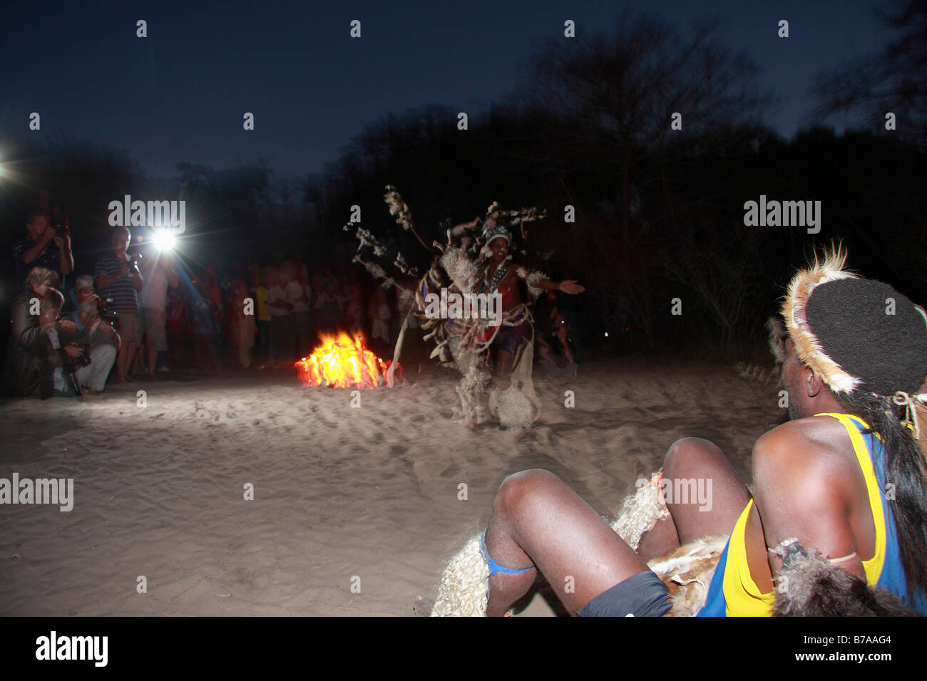 Tourists watching an outdoors Tonga dance performance at night - Stock Image