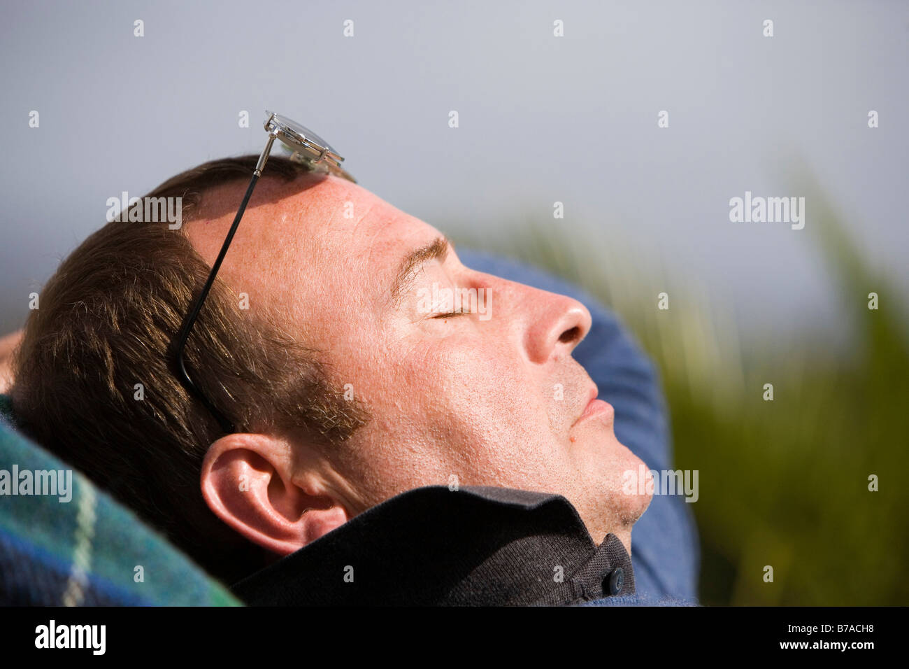45 year old man relaxing in the sun - Stock Image