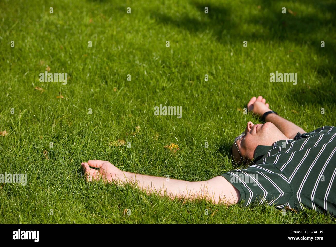 45 year old man enjoying the sun in a meadow - Stock Image