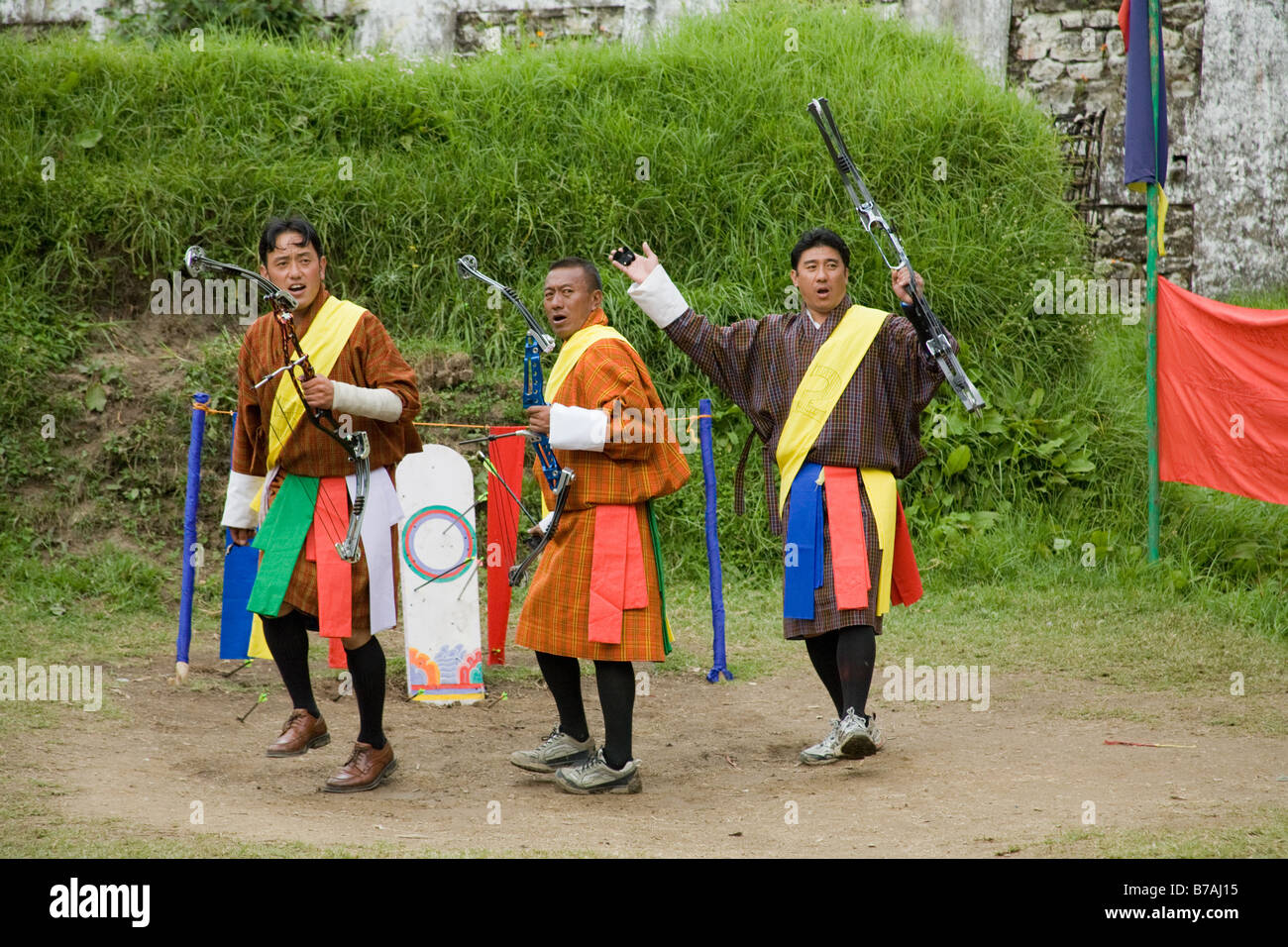 Three archers, at an archery contest taking place on the archery ground besides Trongsa Dzong. They are celebrating Stock Photo