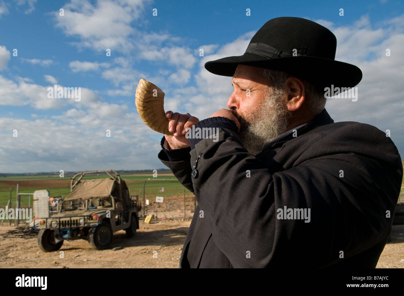 An ultra orthodox religious Jew blowing  the Shofar encouraging IDF troops deployed at the Israeli border with Gaza - Stock Image