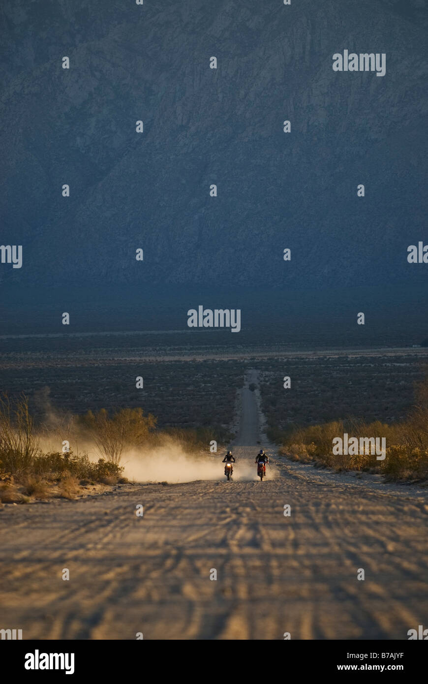 Two offroad motorcycle riders travel down sandy desert road in Baja California, Mexico - Stock Image