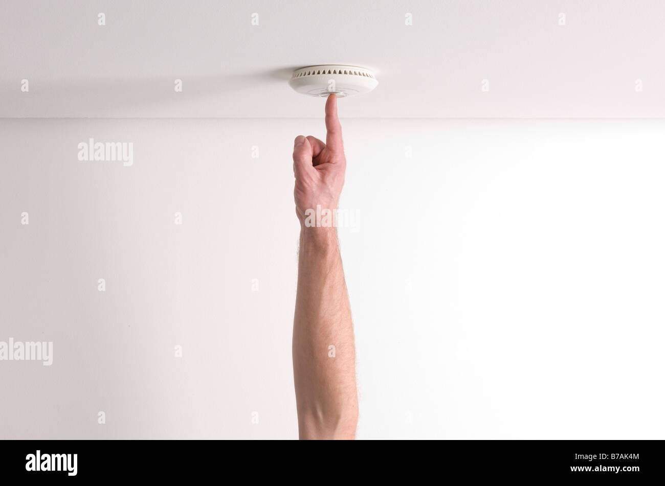 Man testing a domestic fire alarm is working correctly - Stock Image