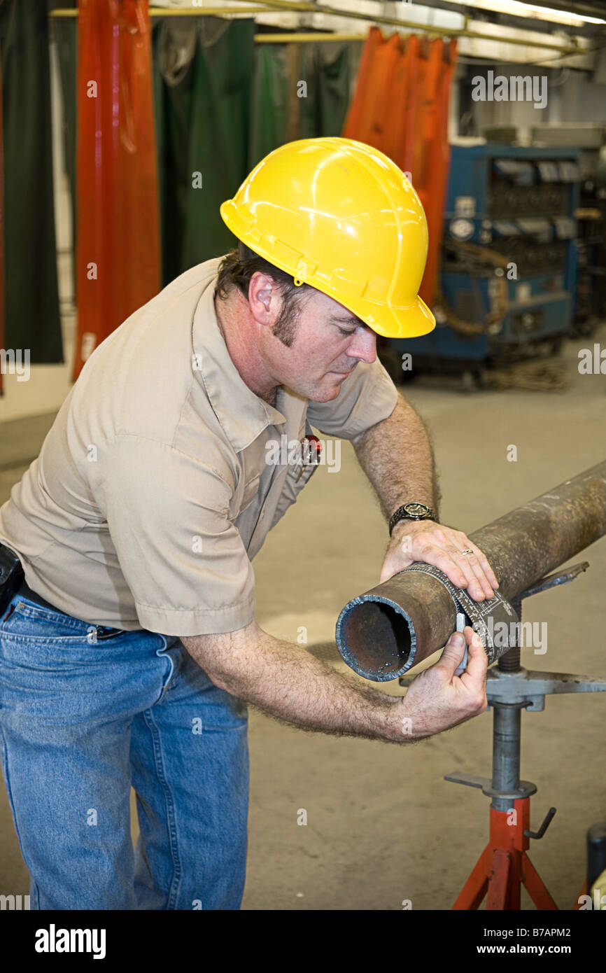 Metal worker using a flexible ruler to measure pipe and mark it for cutting Authentic and accurate content depiction - Stock Image