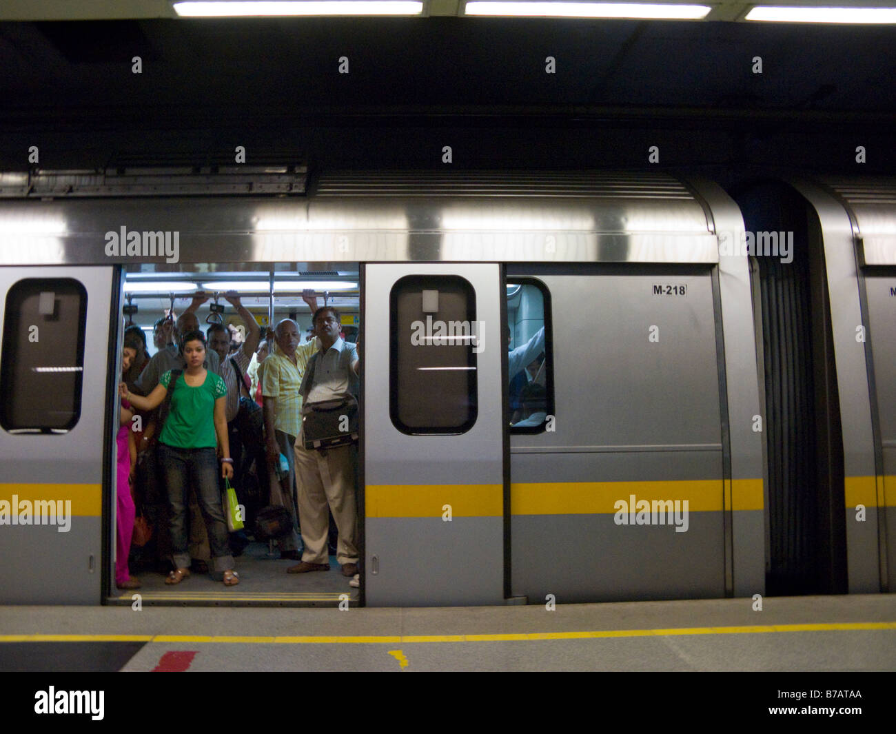 A yellow line tube train carriage with open doors at a platform at Chandni Chowk station. Delhi Metro Rail system. India.(45) & A yellow line tube train carriage with open doors at a platform at ...