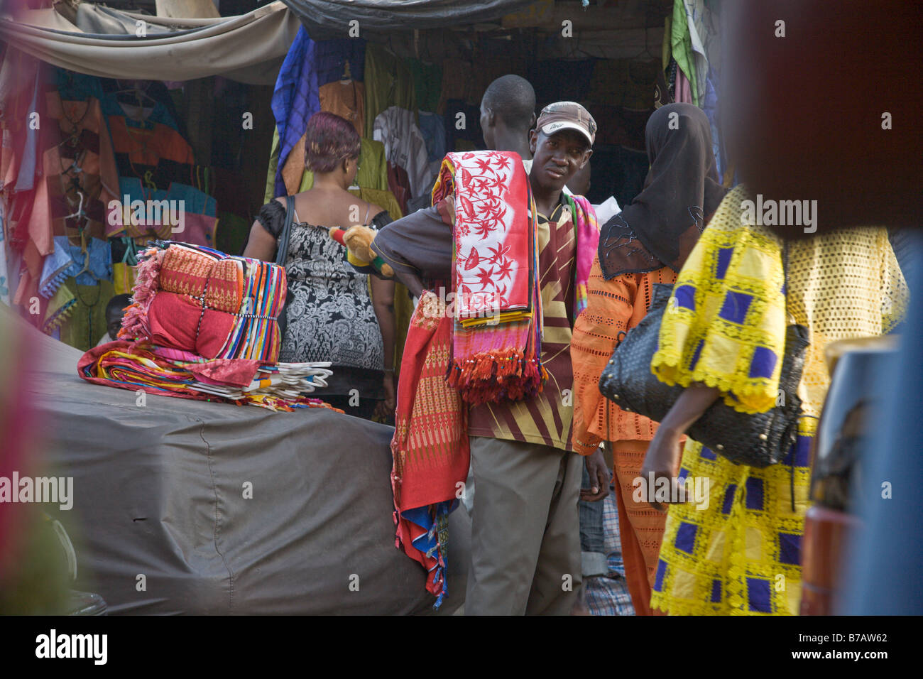 The HLM Market in Dakar, Senegal sells all kinds of colorful cloths.  Many of the vendors come here from Guinea. - Stock Image