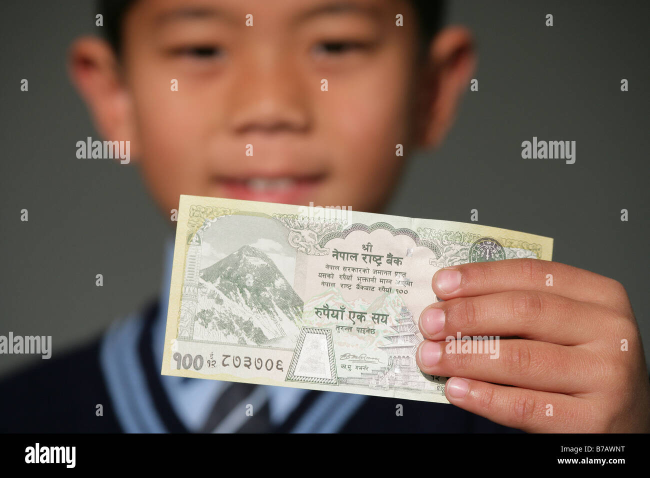 """Nepalese school boys holding a one hundred rupee note"" - Stock Image"