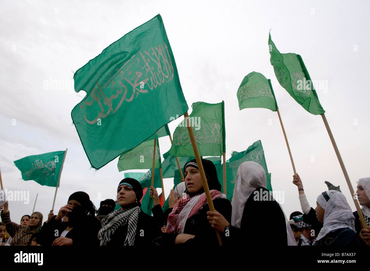 Bedouin women wave green Islamic flags in the Negev village of Ar'arat an-Naqab during a protest against Israel's Stock Photo