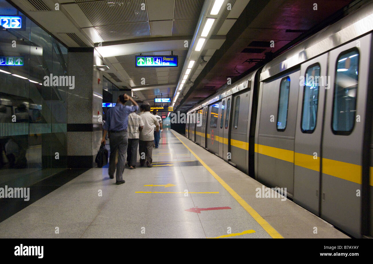 A yellow line train at the platform, & some passengers, at Chandni Chowk station on the Delhi Metro Rail system. - Stock Image