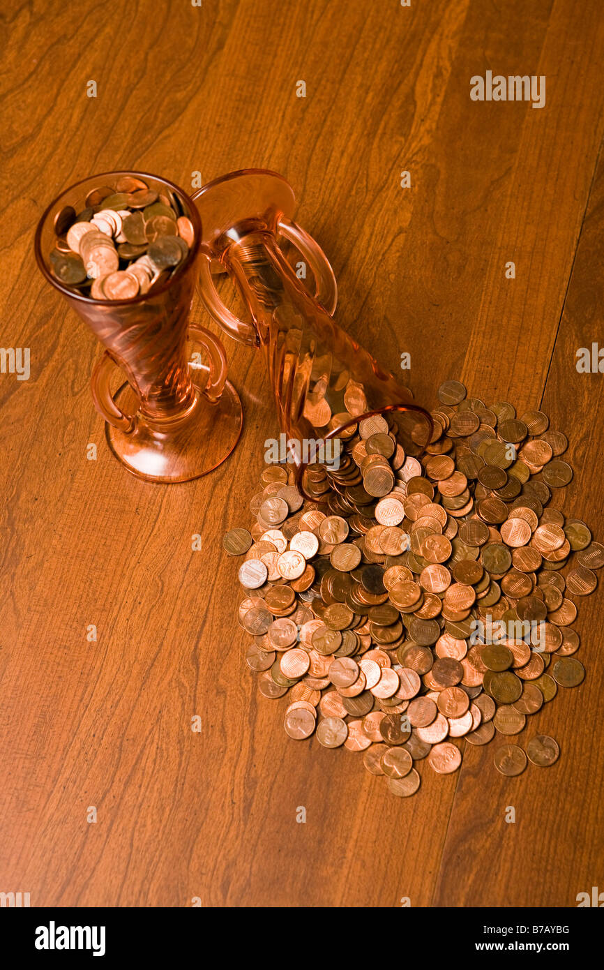 Two vases full of pennies, one dumped out on table. - Stock Image