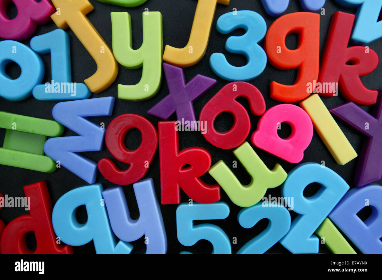 Letters and numbers upside down and back to front on child black board - Stock Image