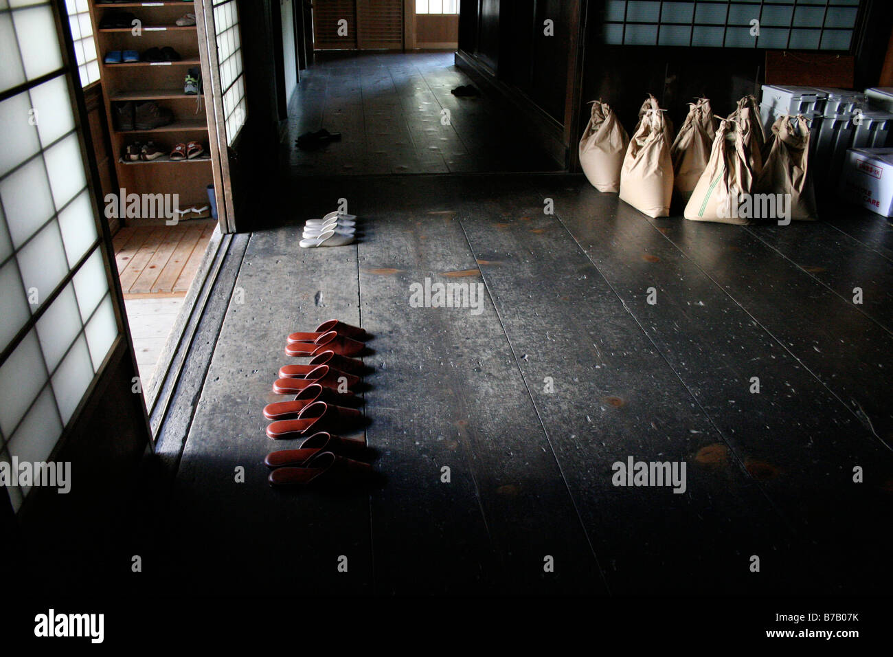Japanese indoor slippers lined up by sliding doors at the entrance to a temple in Koya-san, Japan - Stock Image