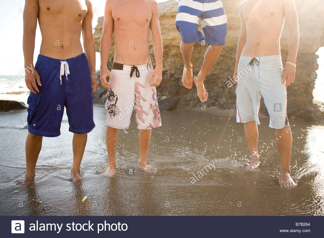 Multi-ethnic group of men standing on beach - Stock Image