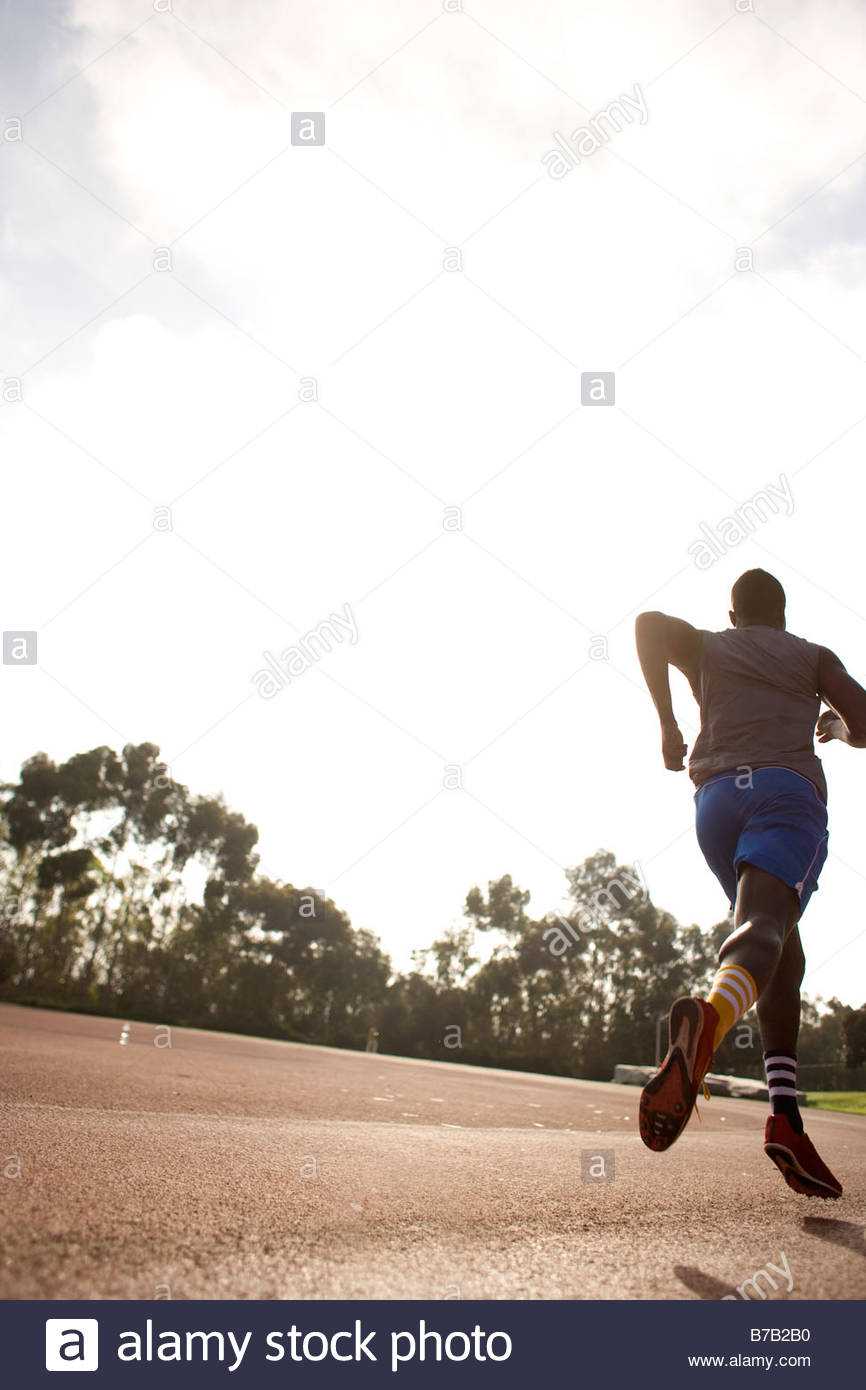 African American man running on track - Stock Image