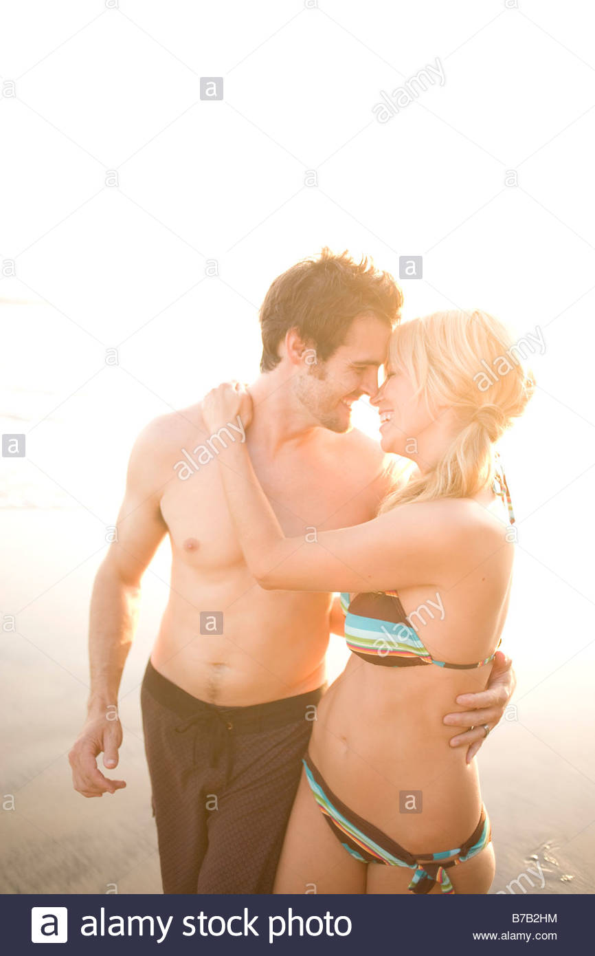 Couple in bathing suits hugging on beach - Stock Image