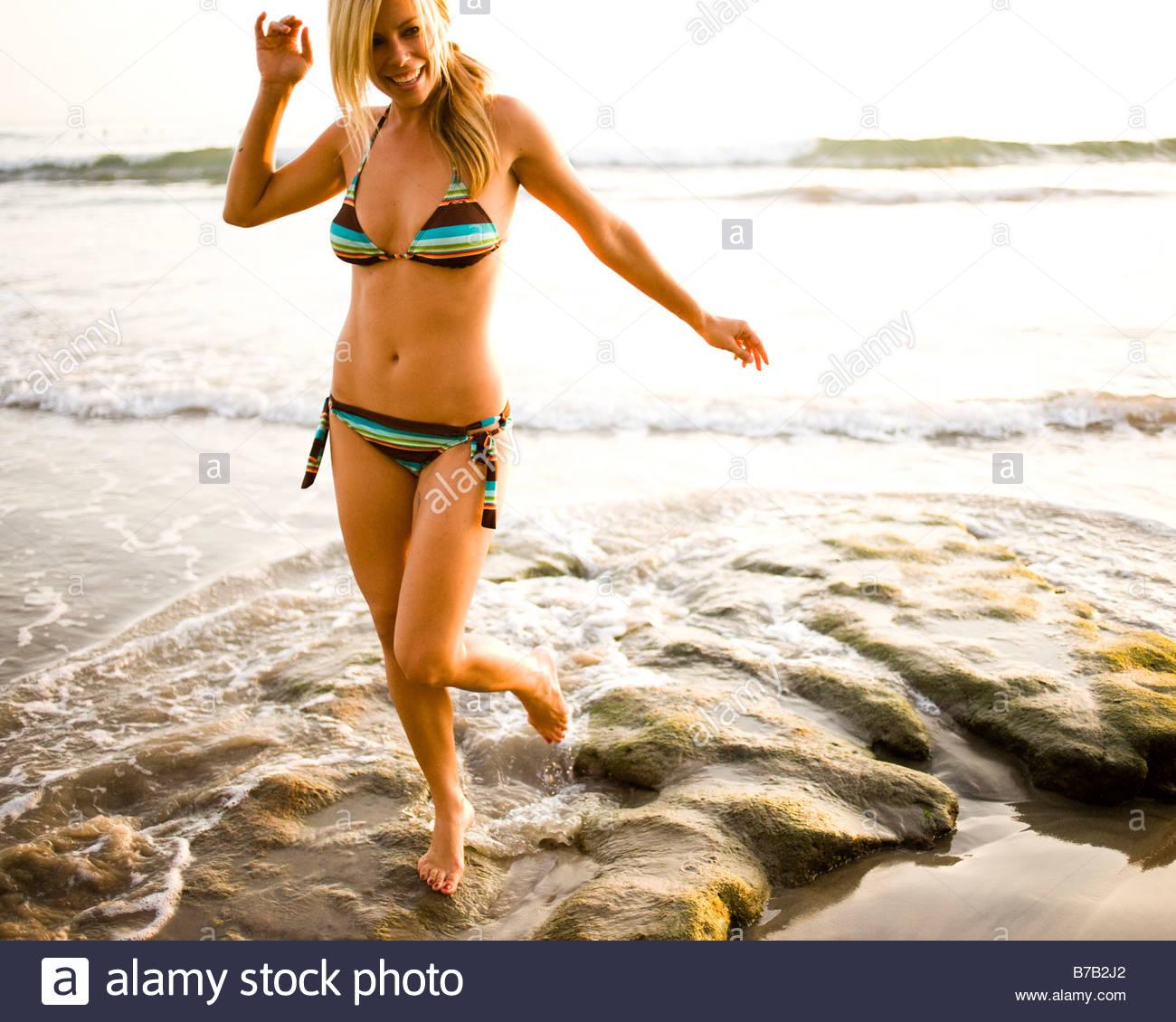 Woman in bikini walking on craggy beach - Stock Image