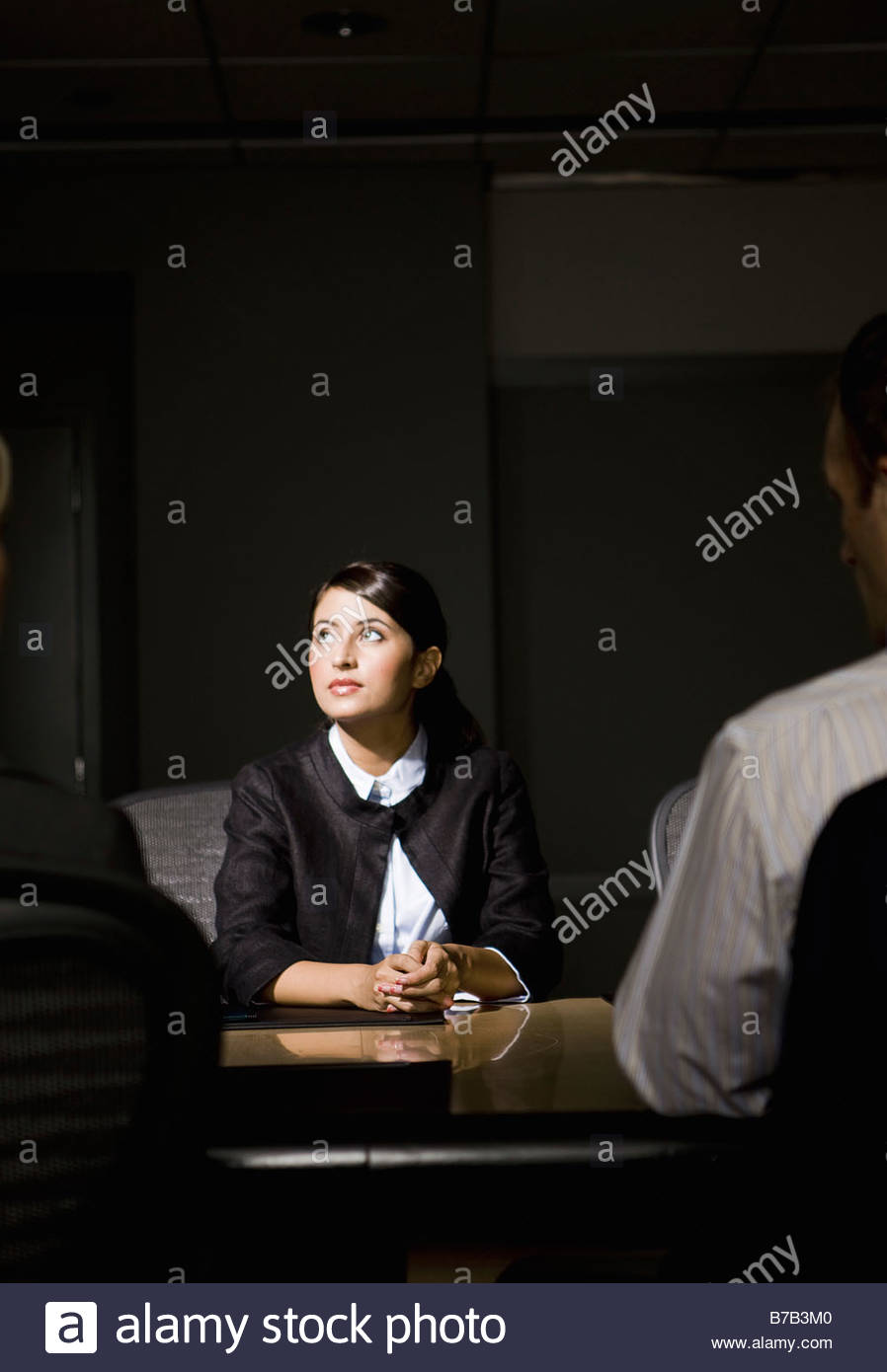 Light shining on Latin American businesswoman in conference room - Stock Image